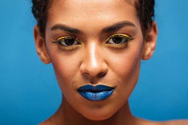 Donna razza mista splendida alla moda del primo piano con i cosmetici variopinti sul fronte che osserva sulla macchina fotografica, isolata sopra la parete blu