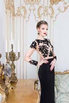 Donna reale bionda in piedi vicino al tavolo retrò in splendido abito di lusso con un bicchiere di vino in mano. interno. copia spazio