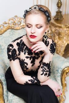 Donna reale bionda seduta su una sedia retrò in splendido abito di lusso, con gli occhi chiusi. interno
