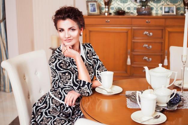 Donna ricca castana in vestito elegante che si siede su una sedia in una stanza con l'interno classico. interno. copia spazio
