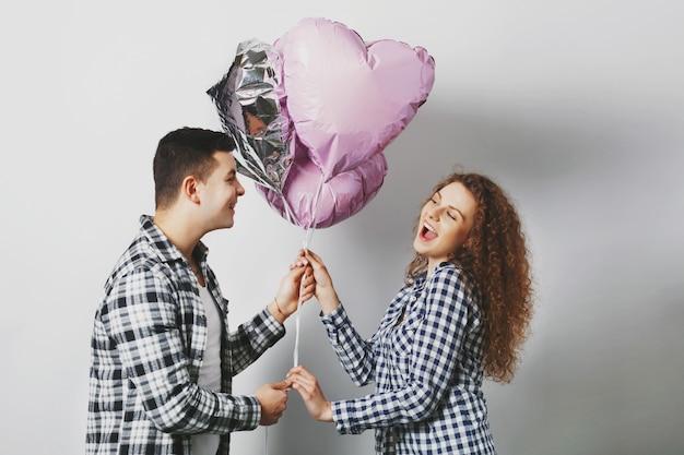 Donna riccia allegra sveglia felice di ricevere i palloncini del cuore dal ragazzo che è molto romantico