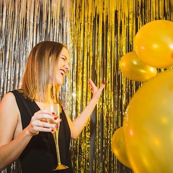 Donna ridente con palloncini alle celebrazioni del nuovo anno