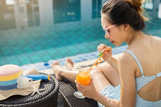 Donna rilassante in piscina, vacanze estive