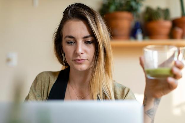 Donna rilassata che lavora da casa sul suo computer portatile