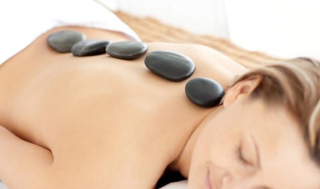 Donna rilassata con pietre calde sulla schiena