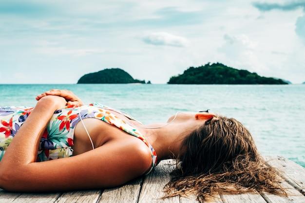 Donna rilassata sdraiata sul molo in legno in riva al mare e ascoltare musica durante le vacanze estive
