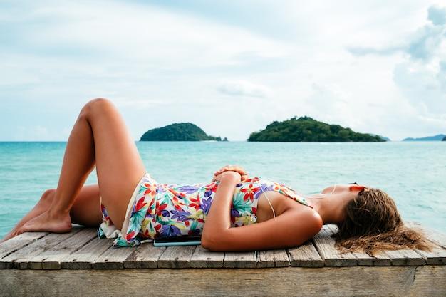 Donna rilassata sdraiata sul molo in legno in riva al mare
