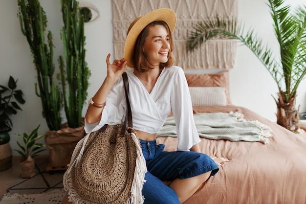 Donna romantica con candido sorriso seduto sul letto, godendo la mattina di sole nel suo elegante appartamento in stile boho