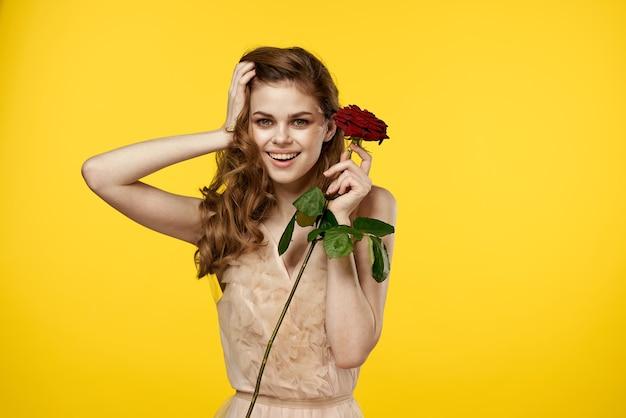 Donna romantica in abito da sera con rosa rossa su giallo