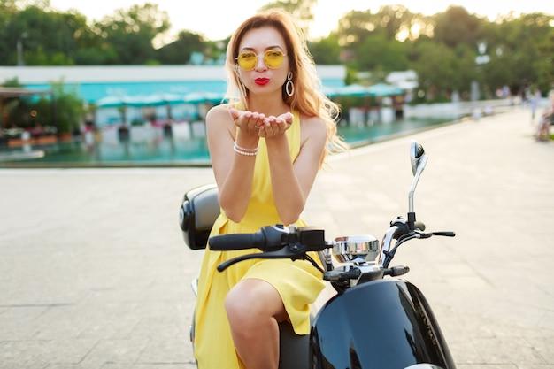 Donna romantica in vestito giallo cavalcando in moto, viaggiando e divertendosi. indossare abiti estivi alla moda. manda un bacio