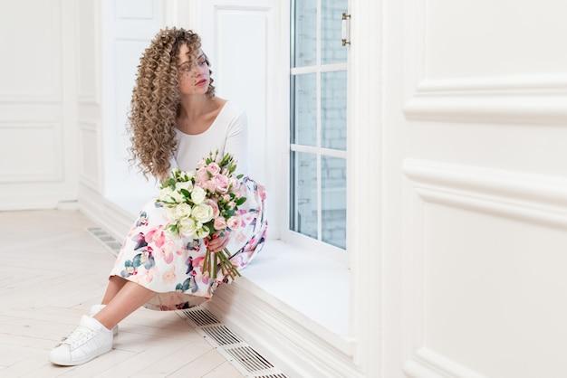Donna romantica sognante che tiene un mazzo dei fiori e che guarda nella finestra che si siede nell'immagine della stanza bianca