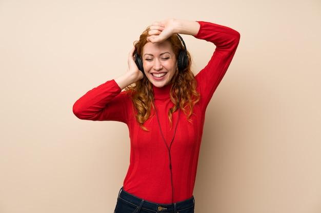 Donna rossa con maglione dolcevita ascoltando musica con le cuffie