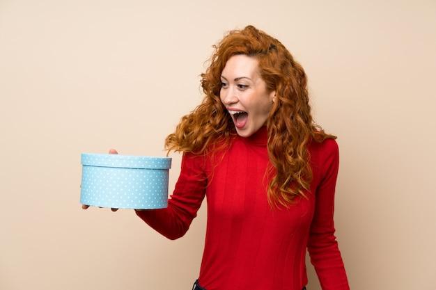 Donna rossa con maglione dolcevita che tiene il contenitore di regalo