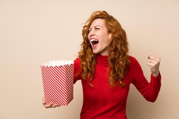 Donna rossa con maglione dolcevita che tiene una ciotola di popcorn