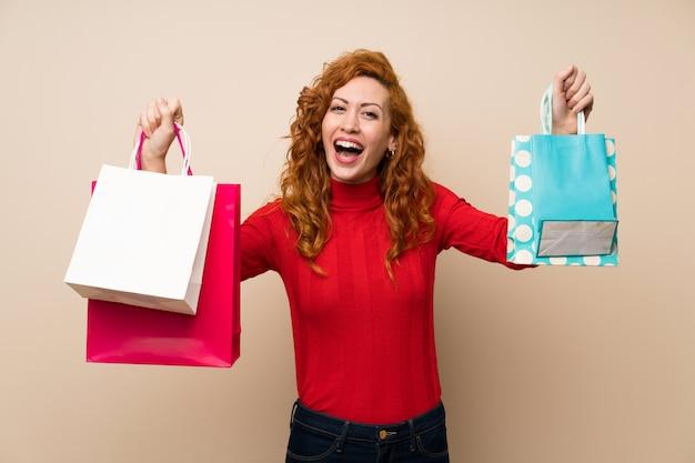 Donna rossa con maglione dolcevita in possesso di un sacco di borse per la spesa
