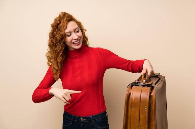 Donna rossa con maglione dolcevita in possesso di una valigetta vintage