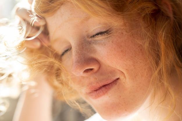 Donna rossa del primo piano con gli occhi chiusi