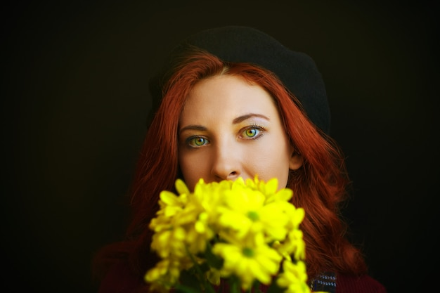 Donna rossa francese in berretto nero tiene e annusa i crisantemi gialli