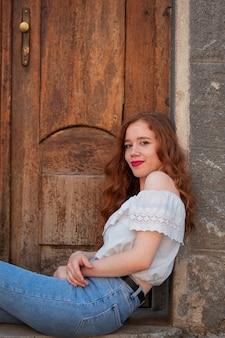 Donna rossa in posa davanti a una porta