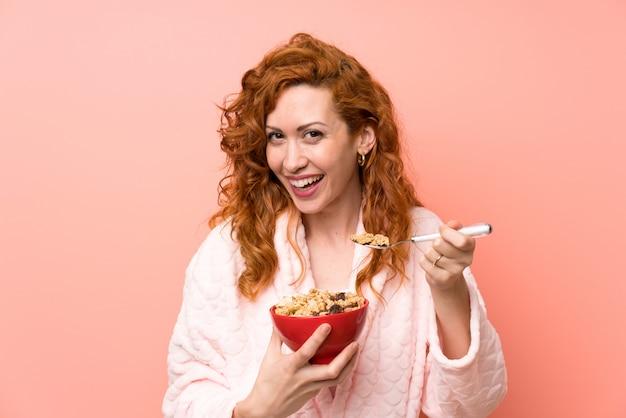 Donna rossa in vestaglia in possesso di una ciotola di cereali