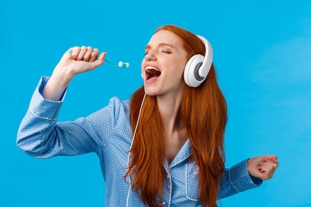 Donna rossa sexy europea appassionata e spensierata in pigiama, chiudere gli occhi indossando le cuffie, ascoltare musica cantando nello spazzolino da denti, lavarsi i denti e prepararsi la mattina, parete blu