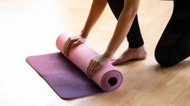 Donna rotolamento tappetino yoga dopo le lezioni
