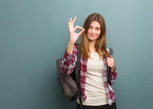 Donna russa del giovane studente allegra e sicura che fa gesto giusto