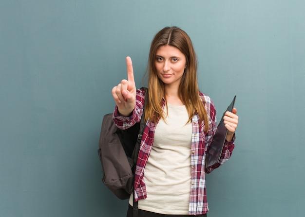Donna russa del giovane studente che mostra numero uno