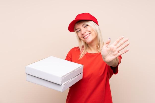 Donna russa di consegna della pizza che tiene una pizza sopra la parete isolata che saluta con la mano con l'espressione felice