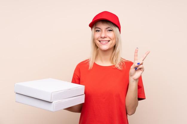 Donna russa di consegna della pizza che tiene una pizza sopra la parete isolata che sorride e che mostra il segno di vittoria