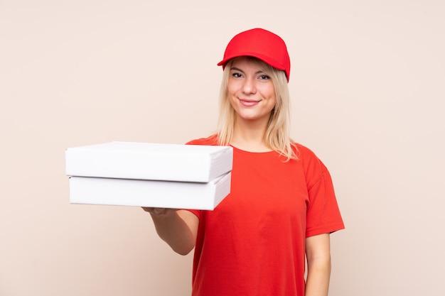 Donna russa di consegna della pizza che tiene una pizza sopra la parete isolata con l'espressione felice