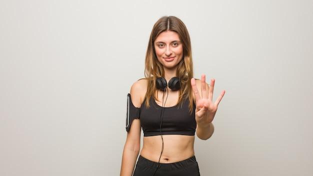 Donna russa di giovane forma fisica che mostra numero quattro