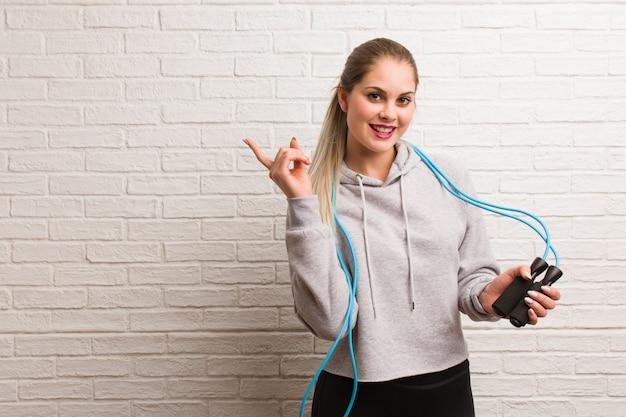 Donna russa di giovane forma fisica che tiene una corda di salto contro un muro di mattoni