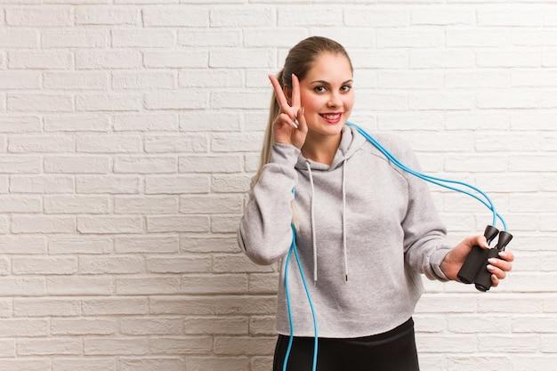 Donna russa di giovane forma fisica che tiene una corda di salto contro una parete di mattoni