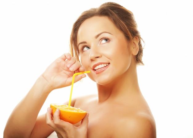 Donna sana di concetto di cibo, dell'alimento e di dieta che beve il succo di arancia