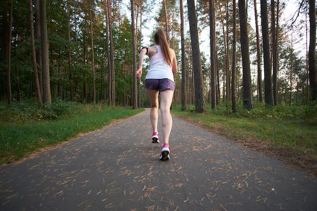 Donna scarna della giovane testarossa che funziona nella foresta di estate. fare jogging al mattino.
