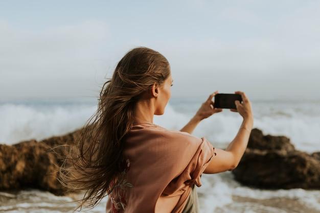 Donna scattare foto con il suo telefono sulla spiaggia