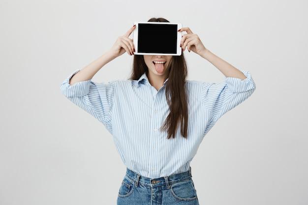 Donna sciocca che mostra la lingua e coprire gli occhi con tavoletta digitale