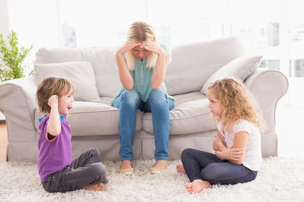 Donna sconvolta che si siede sul sofà mentre fratello che prende in giro sorella