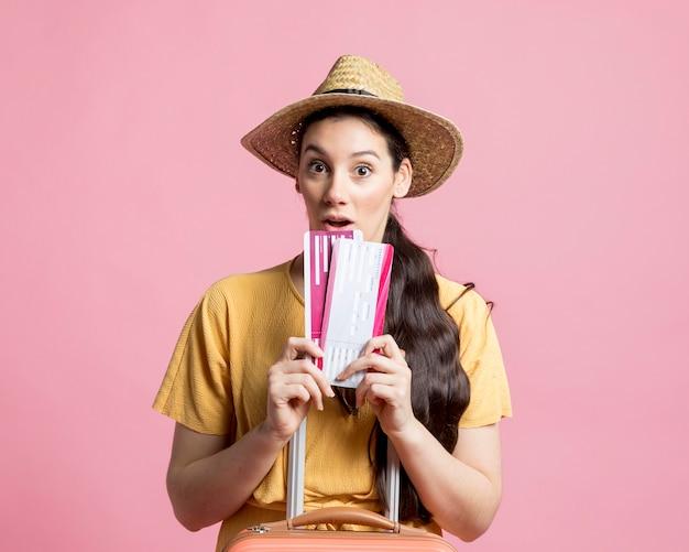 Donna scossa che tiene i suoi biglietti aerei
