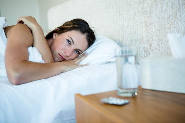 Donna sdraiata a letto accanto all'acqua e pillole sul suo comodino