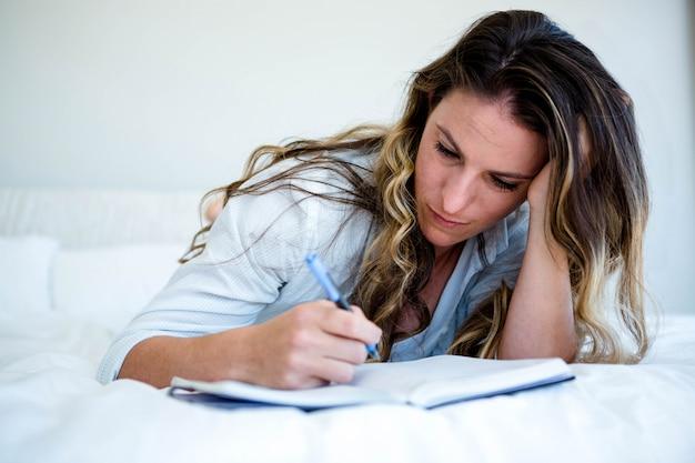 Donna sdraiata nel suo letto, guardando triste e scrivendo in un libro