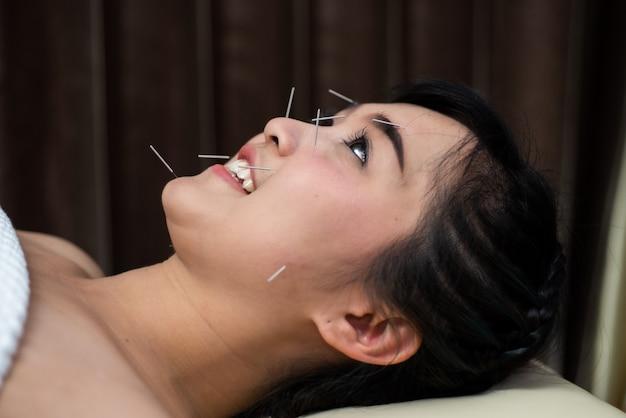 Donna sdraiata su un tavolo in una spa di medicina alternativa con un trattamento di agopuntura e reiki fatto sul viso da un agopuntore