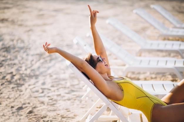 Donna sdraiata sul lettino in riva al mare