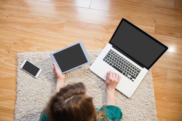Donna sdraiata sul pavimento mentre si utilizza il suo computer portatile e tablet in salotto