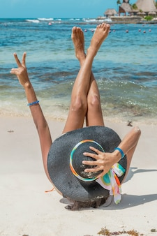 Donna sdraiata sulla sabbia diffondendo gambe e braccia. resort riviera maya, quintana roo, messico