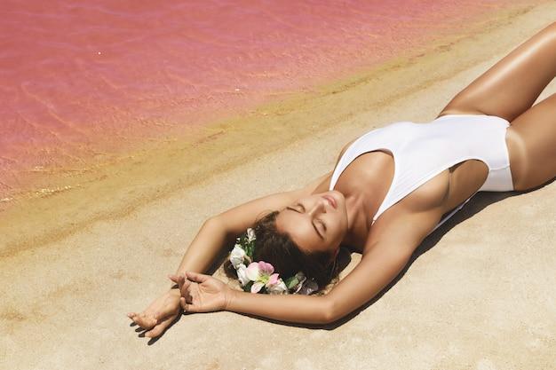 Donna sdraiata sulla spiaggia con acqua rosa