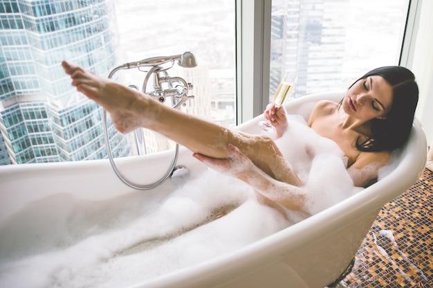 Donna seducente che prende bagno di rilassamento nella sua vasca