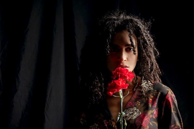 Donna seducente con i fiori rossi nell'oscurità