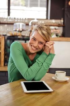 Donna seduta a un tavolo seduto e sorridente